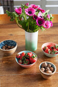 Vase of pink anemones and bowls of strawberries and nuts