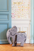 Old wooden elephant toy in front of wainscoting