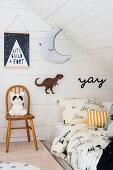 Stuhl mit Vintage Panda-Lampe neben Bett im Dachgeschoss-Kinderzimmer