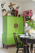 Black dining set in front of green cabinet and kitsch decorations