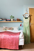 Dress on clothes hanger hung from peg next to bed with pink quilt