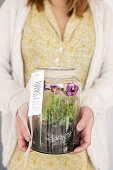 Woman holding jar of violas as thank-you gift