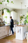 Woman standing in white kitchen with many house plants