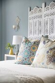Scatter cushions on white double bed with ornate headboard