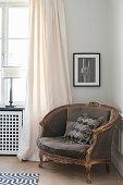 Grafisch gemustertes Kissen im antiken Sessel neben dem Fenster