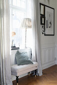 Upholstered bench below window in panelled wall