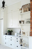 Ample storage and vintage ornaments in bright country-house kitchen