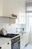 Nostalgischer Gasherd in heller Landhausküche mit weißen Fronten