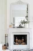 Classic mantelpiece and large mirror above open fireplace