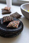 Floral cushions on black designer stool