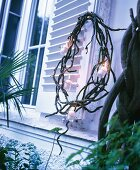Wreath of branches and fairy lights hung from shutter
