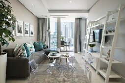 Couch, Ghost chairs and white ladder-style shelves in elegant living area