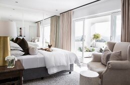 Elegant bedroom with view of summery terrace