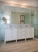 White washstand below mirrored cabinet on marble wall