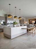Island counter and dining table in elegant open-plan kitchen-dining room