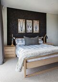 Double bed below framed pictures on black structured wall in bedroom