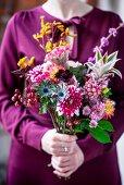 Frau hält Blumenstrauss in leuchtenden Herbstfarben in den Händen