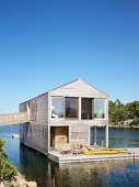 Two-storey wooden house with terrace floating on lake
