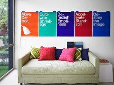 Gemütliches Polstersofa mit verschiedenen Kissen und bunte Wanddekoration mit Grafikdesign-Postern