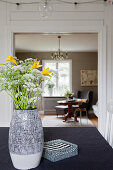 Garden flowers on table with view into living room