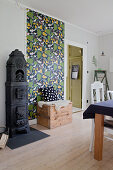 Old cast iron stove and retro wallpaper in rustic dining room