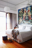Double bed under large-format painting in the bedroom