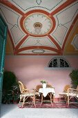 Rattan furniture in lounge area with artistic ceiling design