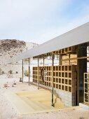 Unusual façade design with steps leading to sunken entrance in desert landscape