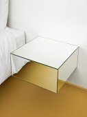 Mirrored floating bedside cabinet mounted on wall next to bed