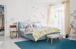 Gepolstertes Doppelbett mit Kleiderbank auf türkisfarbenem Teppich in hellem Schlafzimmer