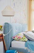 Hellblaues Doppelbett mit gepolstertem Kopfteil, daneben Stuhl als Nachttisch mit Klemmlampe