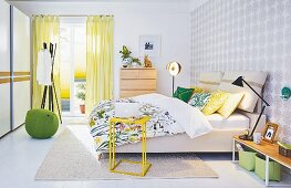 A springlike bedroom with double bed, different lamps and storage space