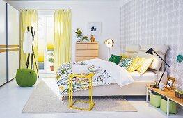 Frühlingshaftes Schlafzimmer mit Doppelbett, verschiedenen Lichtquellen und Stauraum