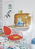 Wandsekretär und roter Designerstuhl im Schlafzimmer