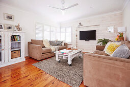 Upholstered set and rollable pallet table in the living room with white painted wooden wall