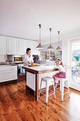 Mutter und Tochter in weisser, offener Küche mit Holzboden