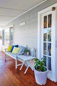 Holzbank mit bunten Kissen, Beistelltisch und Topfpflanze auf der Veranda