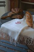 Bread knife, chopping board and bread on embroidered white cloth