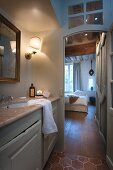 View from illuminated bathroom into bedroom with traditional ambiance