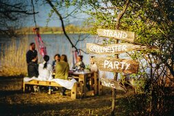 Rustic hand-made signpost with lettering on wooden boards for summer party
