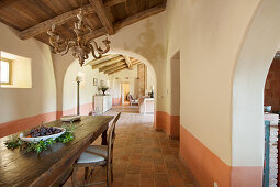 Long wooden table in dining room with arched doorways