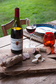 Salami and cheese on wooden board and bottle of wine on table in garden