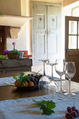 Wine glasses and fruit on table in Mediterranean country-house kitchen