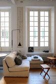Helles Polstersofa, Beistelltische und Stehleuchte vor Sprossenfenster in Altbauwohnung