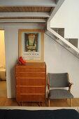 Grauer Polsterstuhl neben Kommode und Plakat unter Treppenaufgang