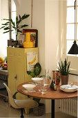 Gedeckter runder Tisch vor Fenster und Metallschrank in der Küche