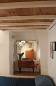 Blick über Bett auf 50er Jahre Kommode mit Wandpsiegel und Hocker
