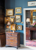 Antique gilt-framed pictures on blue wall above old wooden chest of drawers