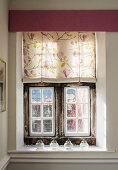 Floral fabric roller blind on antique lattice window