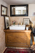 Countertop sink on old wooden washstand in bathroom with low ceiling